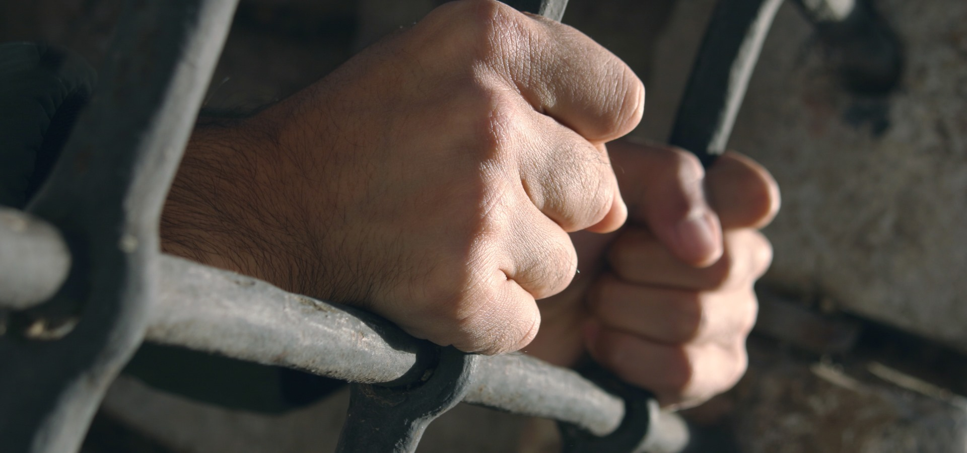 hands grabbing prison bars