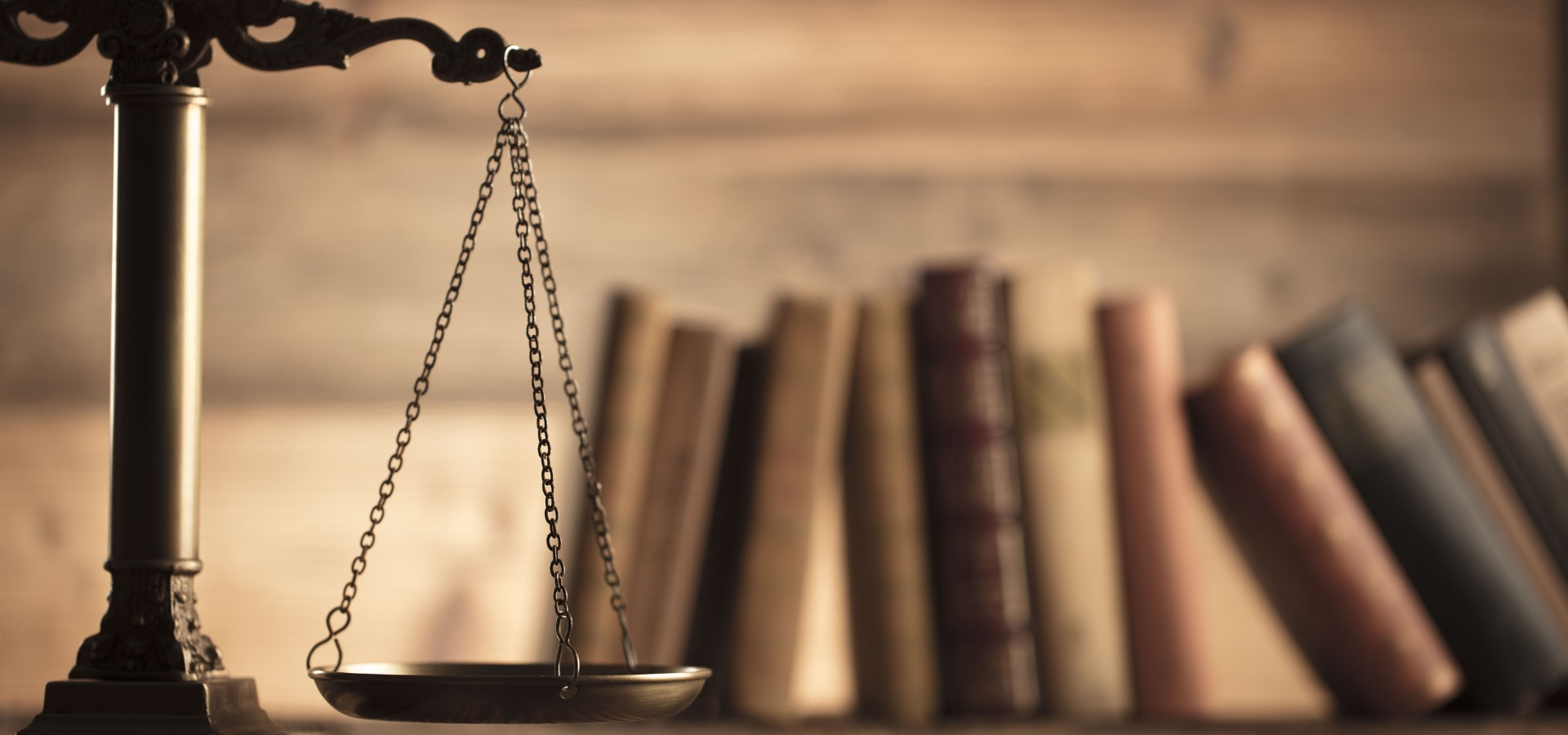 Law and justice concept – scale of justice and legal code on wooden background